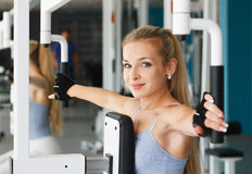 At the fitness club. Young woman doing exercises at the fitness club Royalty Free Stock Photography