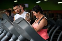 Fitness coach assisting his client on treadmill. Fitness coach assisting his female client on treadmill. Middle aged brunette women working out in modern fitness stock photo