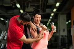 Fitness coach assisting his female client in gym royalty free stock photos