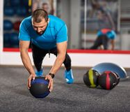 Fitness coach working with medicine ball. Fitness coach demonstrating pushups on a medicine ball in the gym Stock Image