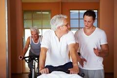 Fitness coach explaining spinning. Exercises to two senior people Stock Photo