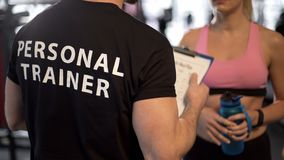 Fitness coach explaining training program and schedule to female client in gym stock photo