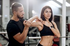 Fitness coach explans to athletic girl dressed in black sport clothes how works muscles of the arms royalty free stock images