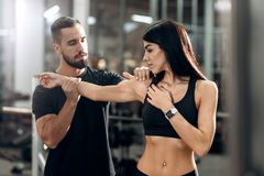 Fitness coach explans to athletic girl dressed in black sport clothes how works muscles of the arms royalty free stock image