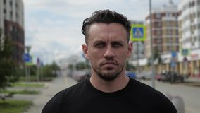 The fitness coach frowns angrily. Portrait on the background of the street. Motivating a harsh look stock video