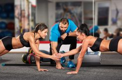 Fitness coach and girls doing workout. Fitness trainer and girls doing crossfit workout in the gym Stock Image