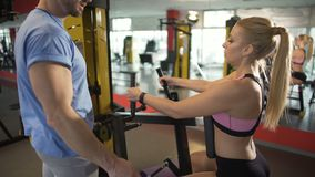 Fitness coach giving advice to his female client, teaching how to do exercise stock video
