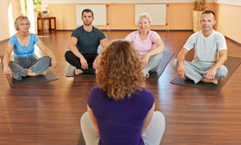 Fitness coach giving yoga. Fitness coach giving group yoga instructions in a gym Stock Images