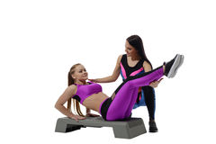 Fitness coach helping girl do exercise on stepper Royalty Free Stock Image