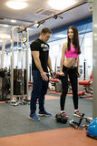 Fitness coach helps girl to choose right exercise Stock Image