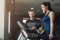 Fitness coach helps woman on elliptical trainer. Fitness instructor helps young women on elliptical trainer. Coach discussing workout plan with girl on treadmill royalty free stock photos