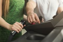Fitness coach helps woman on elliptical trainer stock image