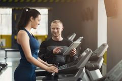 Fitness coach helps woman on elliptical trainer stock photography