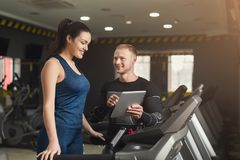 Fitness coach helps woman on elliptical trainer stock photo