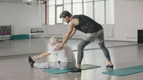 Fitness coach stretching to elderly man in sport club.