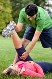 Fitness coach stretching woman's leg. A male fitness coach helping a women stretch her leg at the park Royalty Free Stock Images