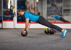 Fitness coach working with medicine ball. Fitness coach demonstrating pushups on a medicine ball in the gym Stock Photos