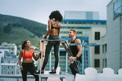 Fitness colleagues standing on rooftop and talking. Fitness men standing with female athletes holding a water bottle and talking standing on rooftop. Man and stock photos