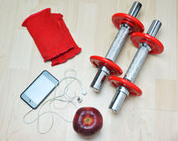 Fitness concept. Adjustable –weight barbells, an apple , pair of weight lifting fingerless gloves, music and headphones on wooden background Royalty Free Stock Images