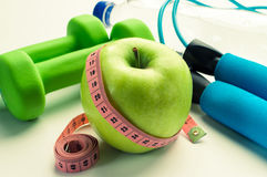 Fitness concept - apple with dumbbells, measuring tape and stethoscope Stock Photo