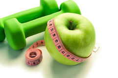 Fitness concept - apple with dumbbells, measuring tape and stethoscope Stock Images