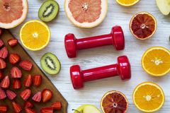 Fitness concept. Assortment of different colorful fruits with dumbbells, top view. Flat lay royalty free stock photography