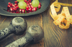 Fitness concept with black dumbbells, pomegranate, grapes, centimeter. Fitness background with black dumbbells, pomegranate, grapes, centimeter Stock Image