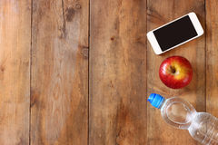 Fitness concept with bottle of water, mobile phone and apple over wooden background. filtered image Stock Images