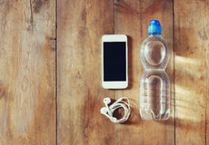 Fitness concept with bottle of water, mobile phone with earphones over wooden background. filtered image Stock Photo