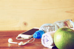 Fitness concept with bottle of water, mobile phone with earphones Royalty Free Stock Photo