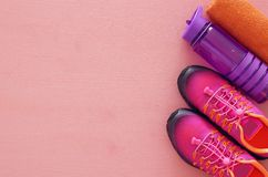 Fitness concept with bottle of water, towel and woman pink sport footwear over colorful background Stock Image