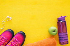 Fitness concept with bottle of water, towel and woman pink sport footwear over colorful background Royalty Free Stock Image