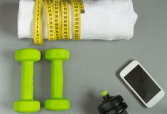 Fitness concept, dumbbell, mobile and a towel and measuring tape, top view Royalty Free Stock Photos