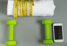 Fitness concept, dumbbell, mobile and a towel and measuring tape, top view Royalty Free Stock Image
