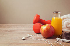 Fitness concept with dumbbells, bottle of juice and smartphone on wooden background Stock Photos