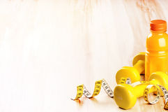 Fitness concept with dumbbells and fresh fruit juice. In yellow tone Stock Photography