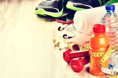 Fitness concept with dumbbells, fruits juice and sportswear Stock Photos