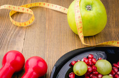 Fitness concept with dumbbells, grapes, apple, pomegranate and centimeter Royalty Free Stock Photo