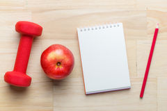 Fitness concept with dumbbells, red apple and blank note. Top view angle with copy space Royalty Free Stock Photo