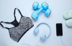 Fitness concept. Flat lay of a smartphone with headphones, plastic dumbbells, sports bra, sneakers on gray background. Top view royalty free stock images