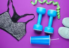 Fitness concept. Weight loss. Sports bra,shoes, dumbbells, ruller,cup on purple background. Top view, flat lay stock photos