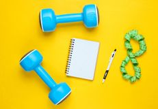 Fitness concept. Workout plan. Plastic blue dumbbells, notepad, ruler on a yellow background. The idea of ​​losing weight. Top view. Flat lay stock photography