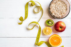 Fitness concept with fruit, bowl of oatmeal and centimeter. Top view background concept. Copy space Stock Photography
