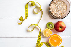 Fitness concept with fruit, bowl of oatmeal and centimeter. Top view background concept. Copy space Stock Photo