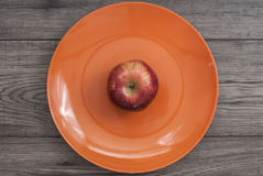 Fitness concept with fruit. Fitness motivation. Apple on plate on wooden table Stock Photography