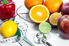 Fitness concept with fruit. Fitness motivation. Fitness concept with fruit, centimeter and stethoscope. Fitness motivation Stock Photos