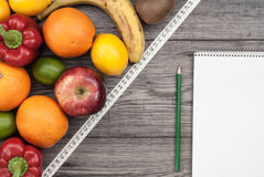 Fitness concept with fruit. Fitness motivation. Fitness concept with fruit, textbook and centimeter. Fitness motivation Stock Images