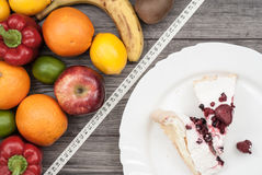 Fitness concept with fruit. Fitness motivation. Fitness concept with fruit vs. plate with cake. Fitness motivation Royalty Free Stock Photo