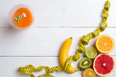 Fitness concept with fruit, a glass of juice and centimeter. Top view background concept. Fitness concept with fruit, bowl of oatmeal and centimeter. Top view Royalty Free Stock Photo