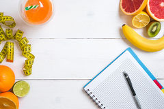 Fitness concept with fruit, a glass of juice and centimeter. Top view background concept. Fitness concept with fruit, bowl of oatmeal and centimeter. Top view Stock Photography